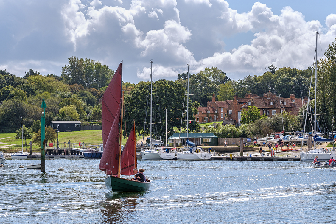 Sailing boat on the Beaulieu River with Buckler's Hard village in the background