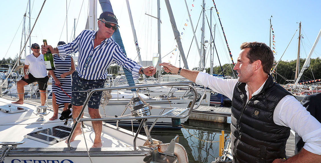 Berth holder gives Sir Ben Ainslie champagne at the 50th anniversary celebration of Buckler's Hard Yacht Harbour
